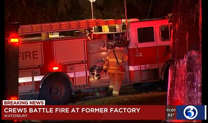 A firefighter prepares to tackle a fire Friday in a vacant Connecticut factory. - Screencapture Via WFSB