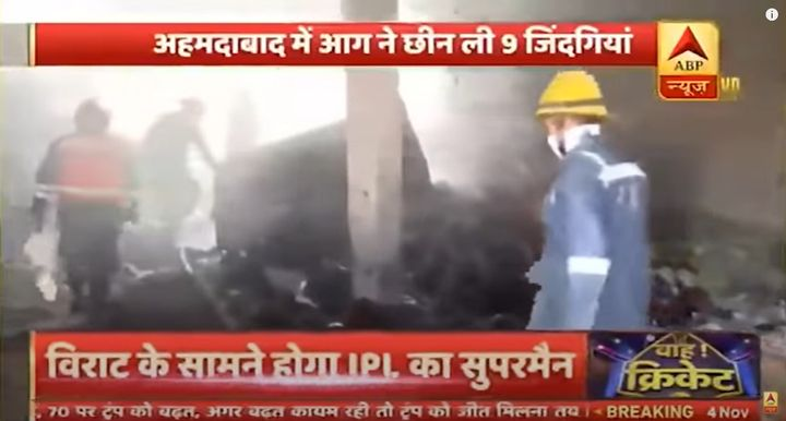 Emergency personnel explore the debris left Wednesday after a textile factory explosion in India. - Screencapture Via ABP News