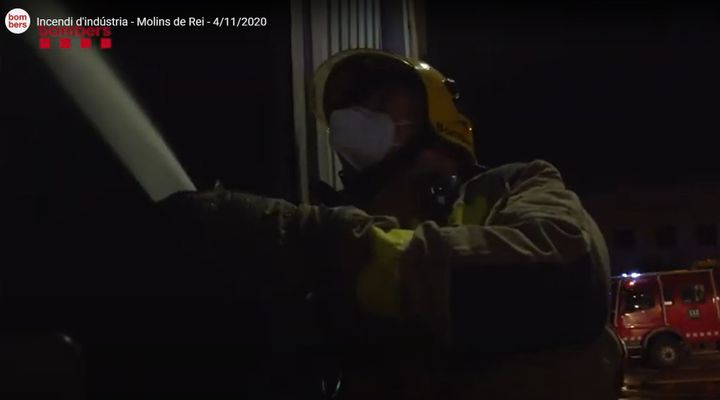 A firefighter in Spain brings water to bear against a burning warehouse Thursday in Barcelona. - Screencapture Via Bombers Generalitat de Catalunya