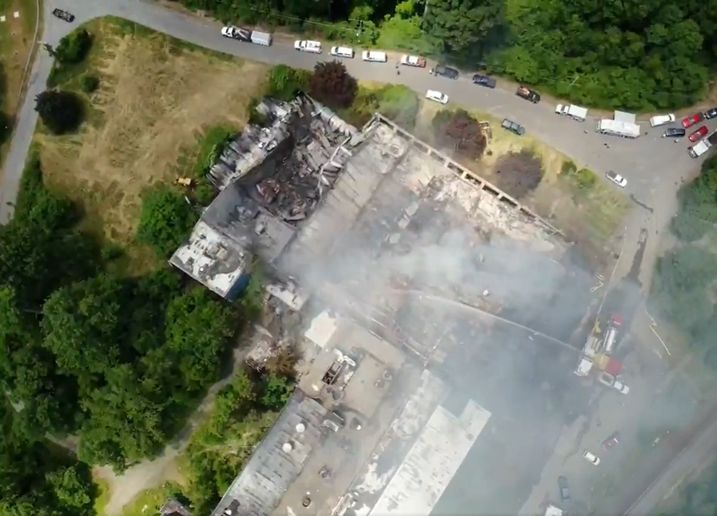 Firefighters apply water to a burned out factory in Massachusetts that caught fire again Monday. - Photo Courtesy of West Branch Aerial Photography