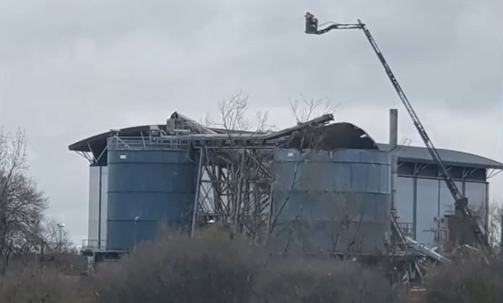 An aerial device is used to observe the damage after an explosion Thursday at a water recycling plant in Avonmouth, England. - Screencapture Via Bristol Live
