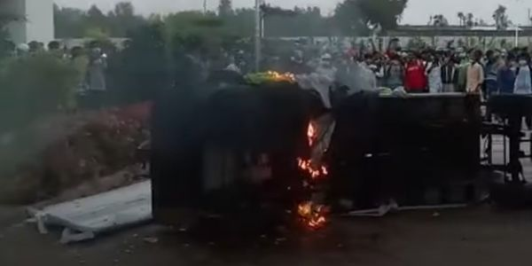 A vehicle burns outside a factory in India wrecked Saturday by rioting workers.