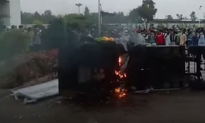 A vehicle burns outside a factory in India wrecked Saturday by rioting workers. - Screencapture Via The Week