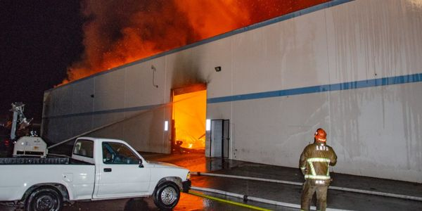 Fire bursts through the roof of a pipeline company Wednesday in Los Angeles.