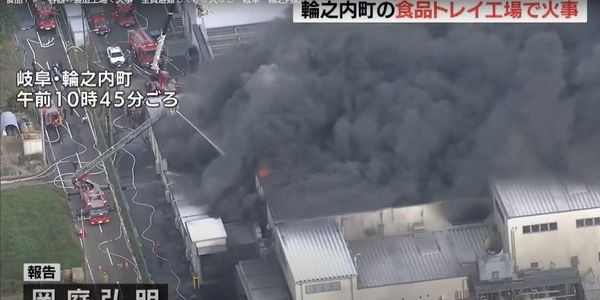 Flames consume the roof of a food container plant Monday in Wanochi, Japan.