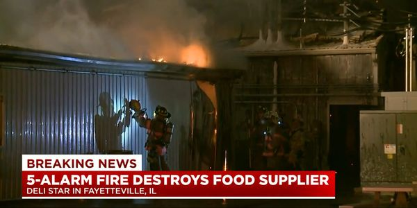 A firefighter cuts through the wall of a meat processing plant that burned Monday night in Illinois.