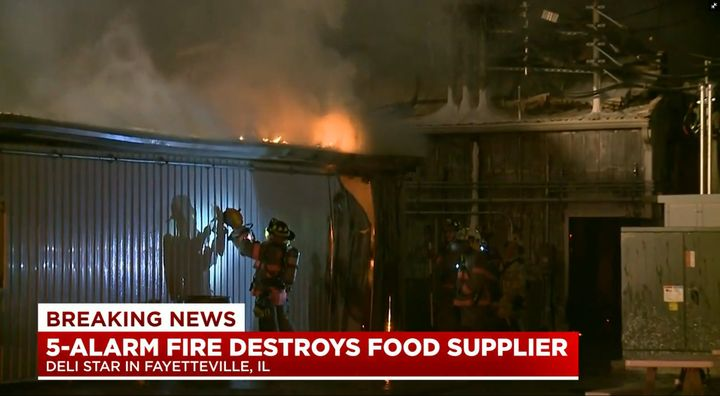 A firefighter cuts through the wall of a meat processing plant that burned Monday night in Illinois. - Screencapture Via KMOV