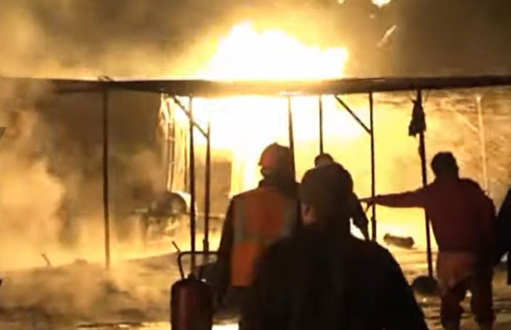 Firefighters move in on one of seven burning crude storage tanks Tuesday in Syria. - Screencapture Via Ruptly
