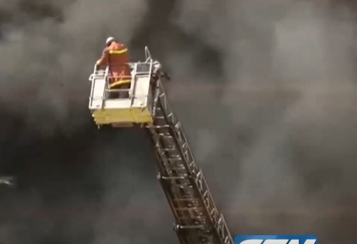 A firefighter atop an aerial ladder surveys the remains of a burning factory in Karachi, Pakistan, Saturday. - Screencapture Via GTV Network