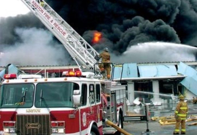 Firefighters swing into action during a rubber components factory fire in January 2003 in Kinston, North Carolina. - Photo by Woody Spencer/Kinston Fire Department