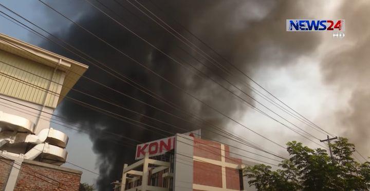 Smokes rises the entire length of the Konka refrigerator factory Sunday in Bangladesh. - Screencapture Via News 24