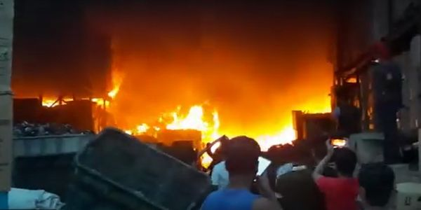 Flames raced through a rubber goods warehouse Saturday in Malaysia.