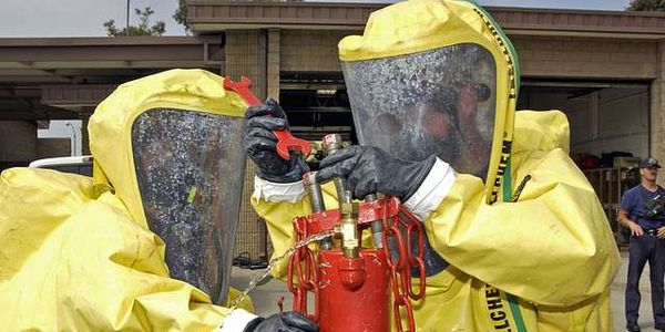 Firefighters secure a simulated leak on a chlorine bottle during a training exercise.
