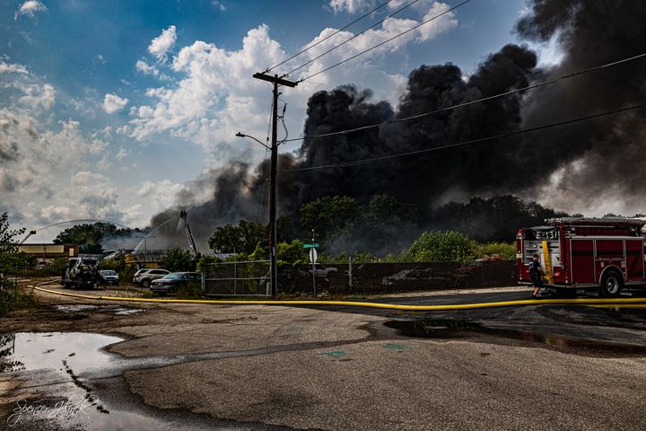 The fire at the warehouse, which stored militarytires, a small amount of chemicals, cardboard and recycling products, continues to burn today with active fires reported throughout the building. - www.facebook.com/spencerjelinekphotography