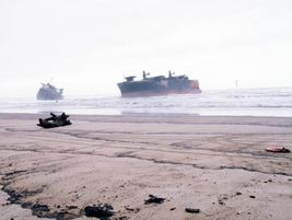 The grounded freighter New Carissa is closely monitored by a Coast Guard vessel in the distance...