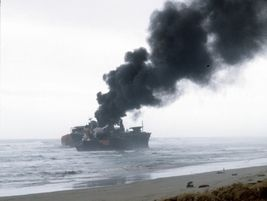 Smoke rises from the stern of the freighter New Carissa after the bulk carrier broke apart in...