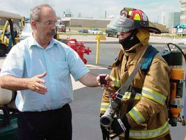 Istvan Szoc (left) demonstrates the Impulse Fire Extinguishing System that uses small amounts of...