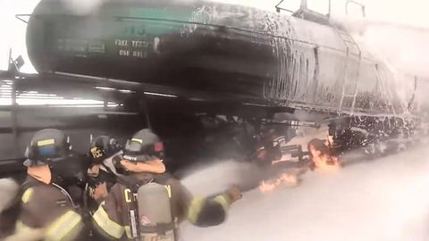 Chevron firefighters close in on the burning Crude by Rail training project at TEEX.