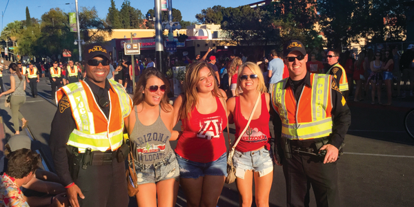 Officers pose for photos with fans, offer up bottles of water during outdoor events, and...