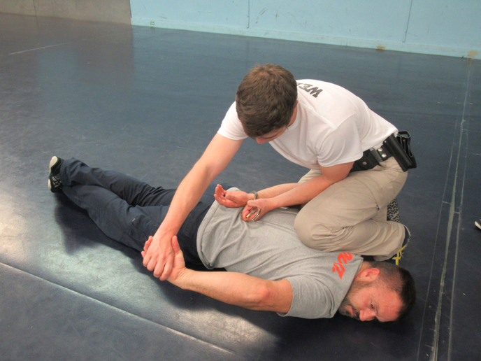 Should the arrestee begin to resist, maintain control by driving the arm downward and apply pain compliance through the wrist manipulation. That said, no tactics work every time; be aware that the control officer may need to disengage.  - Photo: Michael Schlosser