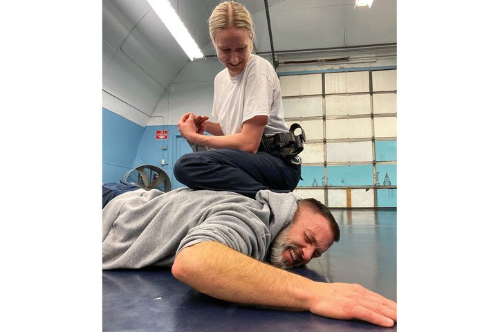 A cooperative arrestee who is high risk can quickly become a resister. If the arrestee begins to resist, the officer can quickly and easily move the arrestee's arm across his/her back and upward beyond the normal flexibility for better control, while at the same time gaining a wrist manipulation for pain compliance. - Photo: Michael Schlosser