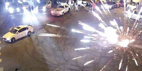 Fireworks are set off in the middle of a blocked off intersection that was the scene of a...