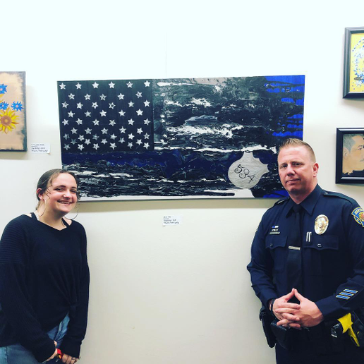 Student artist Alanna Rodriguez stands with School Resource Officer Mitch Brouillette of the Brentwood (CA) Police Department. Behind them is the painting she created and gave to the SRO with whom she has built a friendship.