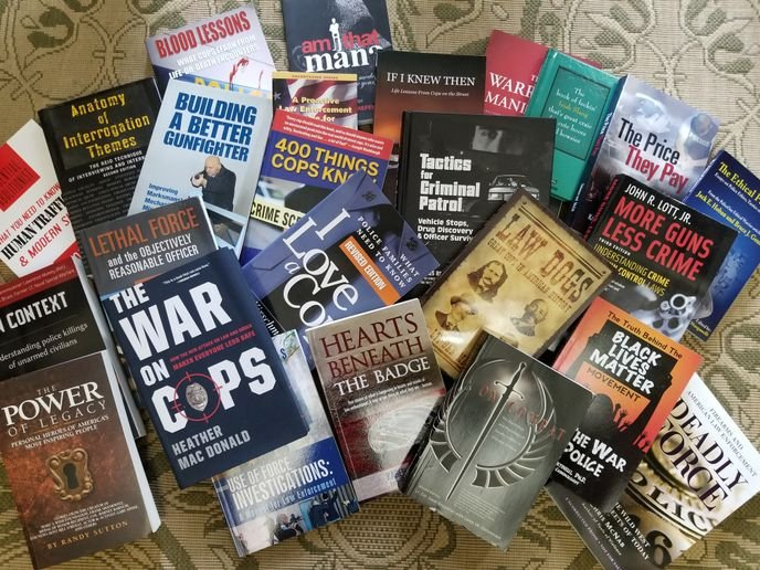 Strewn on my living room floor are a handful of books from my fairly massive collection of law enforcement books and training materials. Image courtesy of Doug Wyllie.