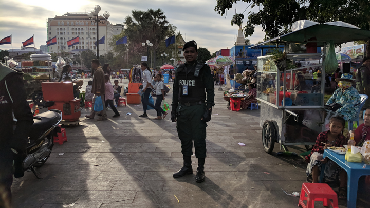An officer in Phnom Penh, Cambodia standing in an open public market.