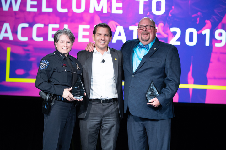 "The recipients of this year's Rise Awards were Sylvia Moir, chief of police in Tempe, (AZ) and Chris Cognac, a recently retired officer who is the co-creator of the ""Coffee With a Cop"" community policing program, flanking Axon President Luke Larson.
