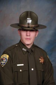 A second responding Trooper found Trooper Wade Palmer shot in his patrol vehicle with his seat belt still fastened.