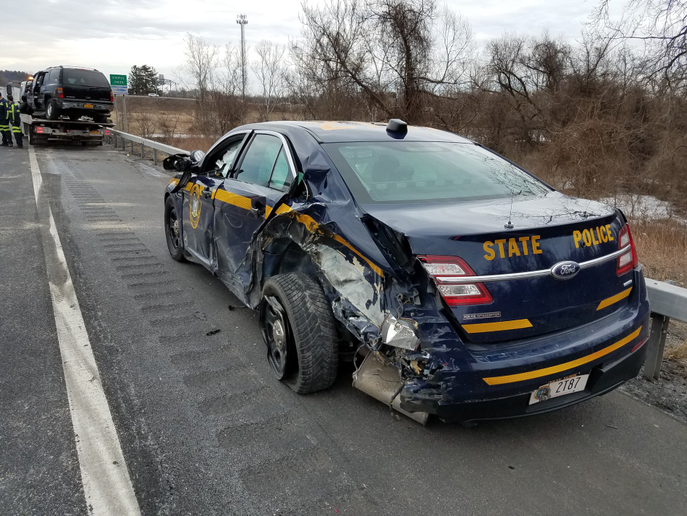 A trooper with the New York State Police suffered minor injuries when a tractor trailer truck struck his vehicle as he was assisting a disabled vehicle.  - Image courtesy ofNew York State Police / Facebook.