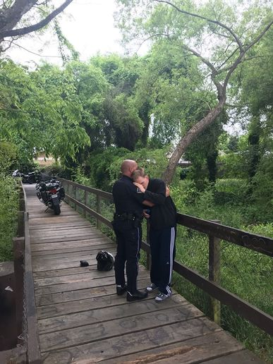 "The agency posted an image of the embrace on Facebook, with the caption, ""Motor Officer Justin Thompson is really feeling the love today after locating a missing resident on the creek path.""