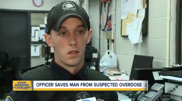 Officer Aaron Franklin freed six teens trapped in a storm drain being filled with rushing waters form a local creek. A short time later, he came upon an unconscious man who had crashed his truck into two cars, administered Narcan, and then performed CPR. (Photo: ABC News Screen Shot)  -