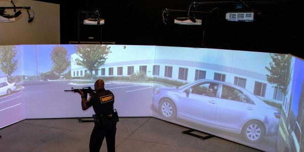 An officer trains using a FATS 300 multi-screen immersive simulator.