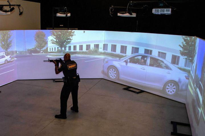 An officer trains using a FATS 300 multi-screen immersive simulator.