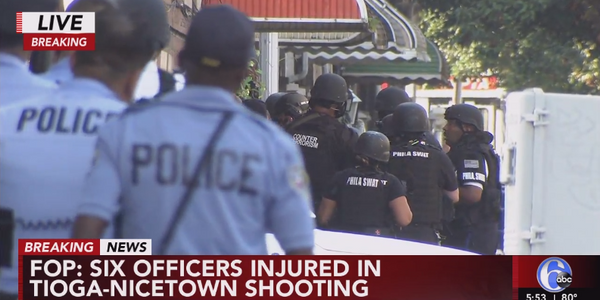 Philadelphia officers outside a home where a standoff is under way. Six officers have been shot....