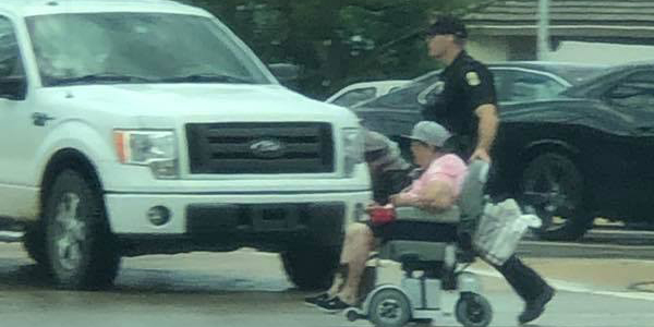 An officer with the Wichita Police Department was seen helping a woman in a wheelchair across a...