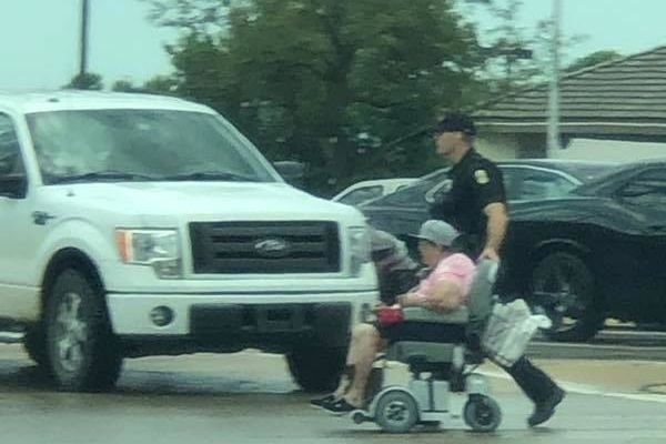 An officer with the Wichita Police Department was seen helping a woman in a wheelchair across a busy intersection over the weekend. Photos of the act of kindness posted to social media quickly went viral.  - Image courtesy ofWichita PD/ Facebook.