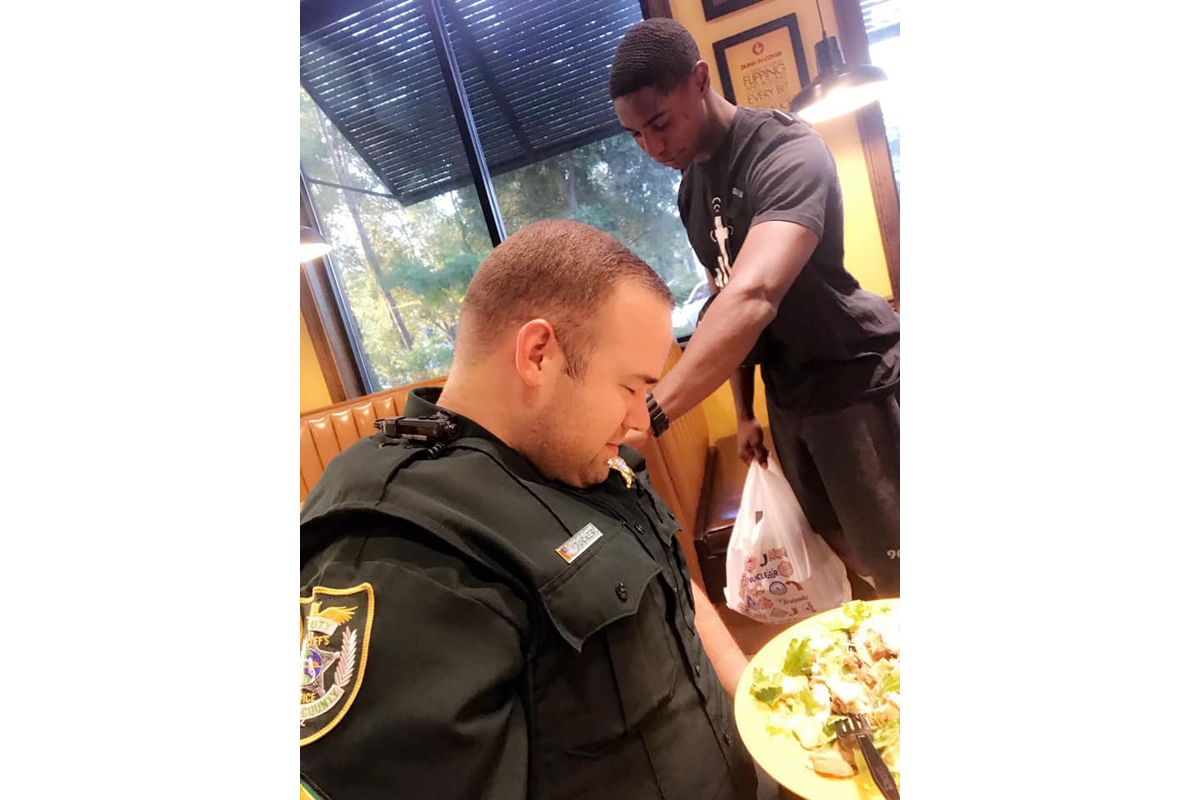 Juan O'Neal approached Officer Cameron Tucker and his wife Justine as they ate a meal at a local restaurant and asked permission to pray for the law enforcement officer.