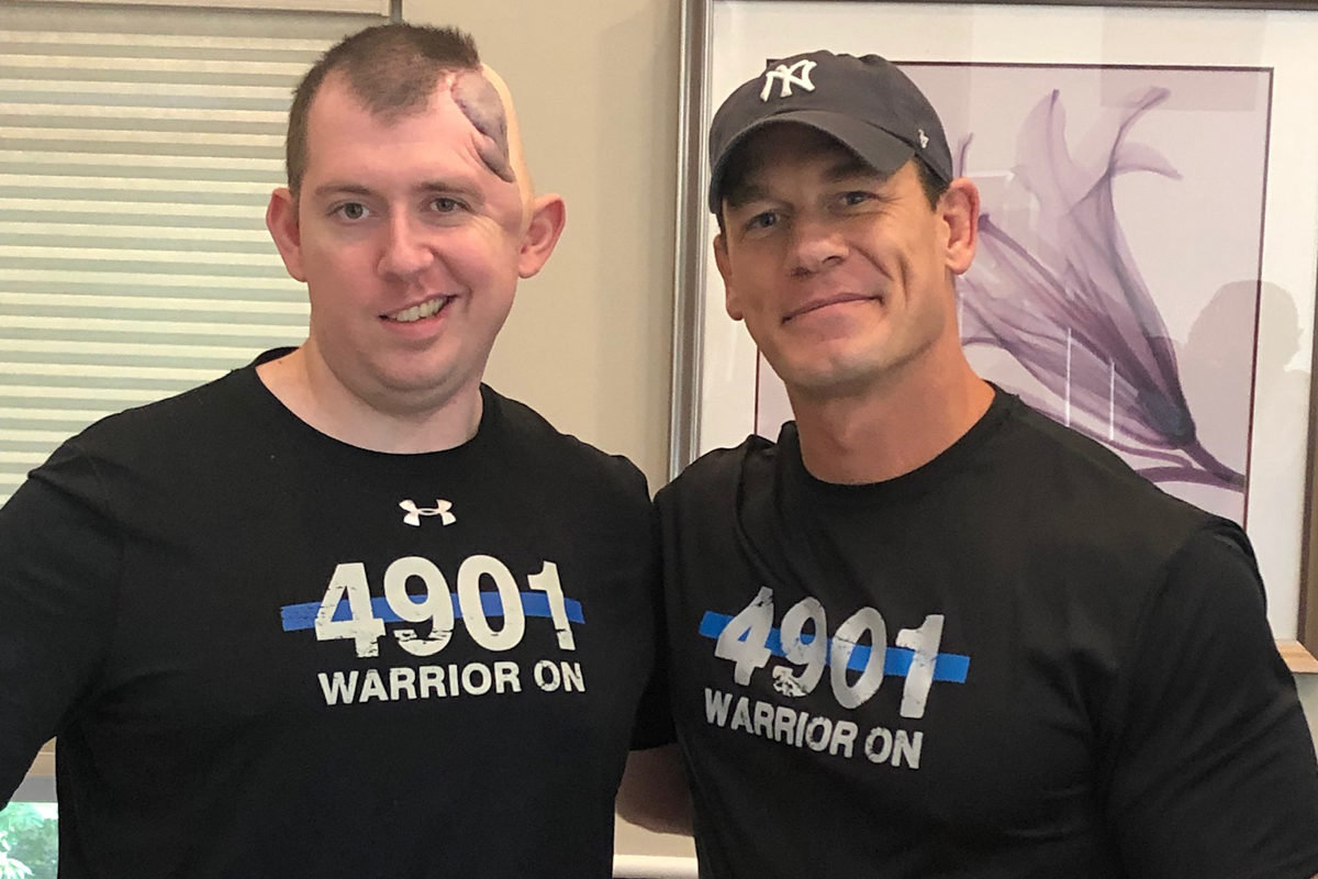 WWE and action movie star John Cena paid a surprise visit to the home of Cam Duzel, a Colorado Springs police officer who suffered a severe gunshot wound to the head in 2018.  - Image courtesy of Colorado Springs PD / Facebook.