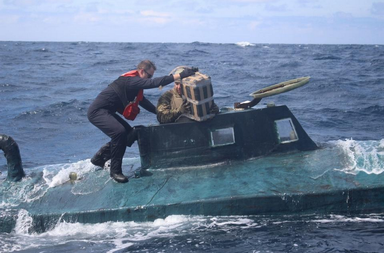 Coast Guard personnel removes cocainse bundles from a captured submarine. (Photo: Coast Guard)