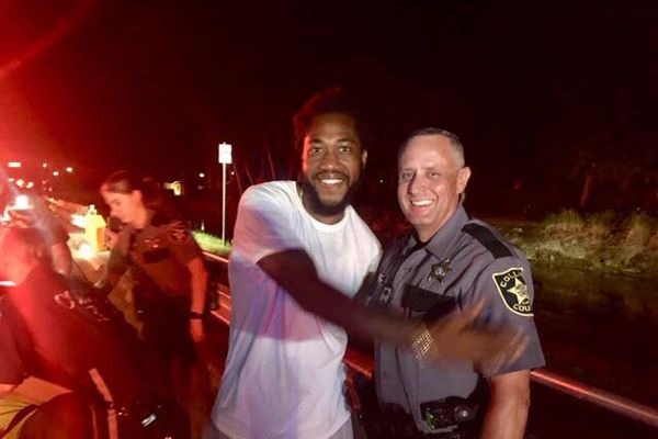 Deputy Robert Pounds the Collier County Sheriff's Officestands beside a happy new dad after helping deliver a baby at roadside.  - Image courtesty ofthe Collier County Sheriff's Office / Facebook.