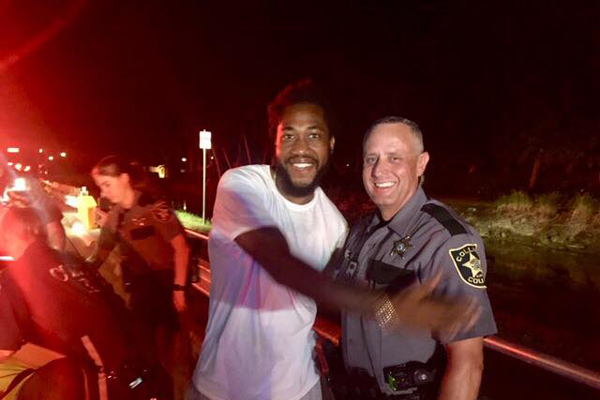 Deputy Robert Pounds the Collier County Sheriff's Office stands beside a happy new dad after helping deliver a baby at roadside. 