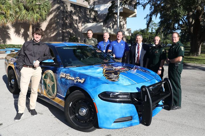 Curtis Moore (left)—a student at Palatka High School—was the artist with the winning design for a uniquely painted patrol vehicle for the school's resource officer, Deputy Doug Kennedy.