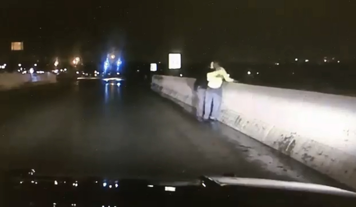 Screen grab of video showing Ohio deputy saving suicidal man from jumping off overpass.