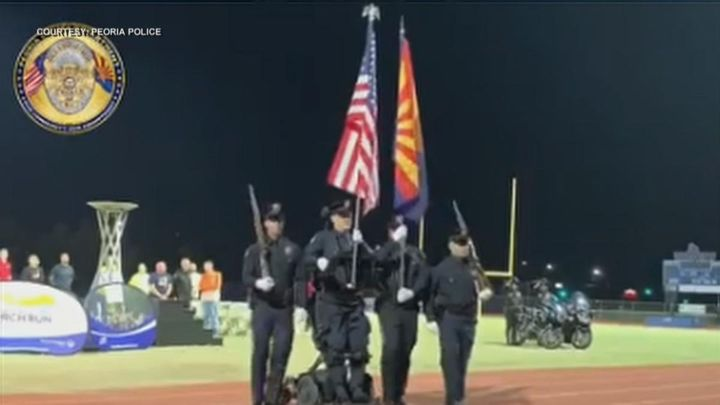 Paralyzed Peoria (AZ) Police Officer William Weigt (holding U.S. flag) stands for the first time in 14 years while serving on the honor guard for the Arizona Special Olympics. (Photo: Peoria PD)