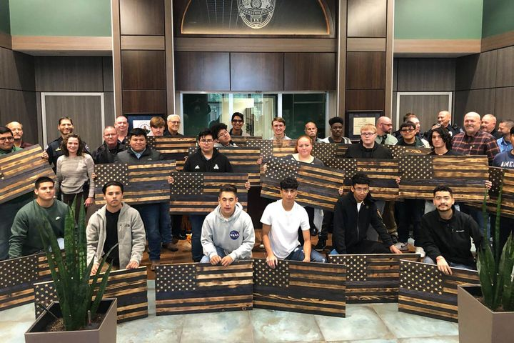 "Students attending Waxahachie High School presented 98 handmade wooden ""Thin Blue Line"" flags to their local police department in a show of respect for the officers who work there and solidarity with the department. - Photo: Waxahachie (TX) Police Department / Facebook"