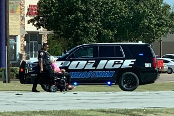 Officer Chris Douglas saw a woman attempting to cross the busy intersection and decided to stop his vehicle in the roadway to block traffic. - Image courtesy of Denise Jones DelVecchio / Facebook.