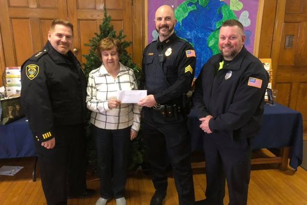 Deputy Chief of Police David Clark, Reading Food Pantry Coordinator Phyllis Maxwell, Sergeant Chris Jones, and Officer Mike Scouten celebrate the holidays with a generous donation to families in need. - Image courtesy of Reading PD / Facebook.